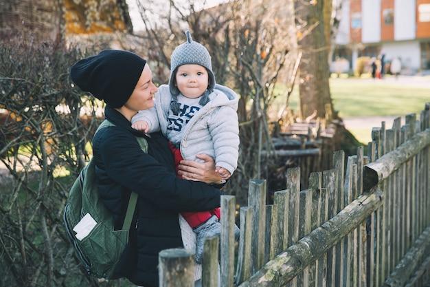 Mãe com seu bebê vestido com roupas quentes caminhando em um dia ensolarado ao ar livre