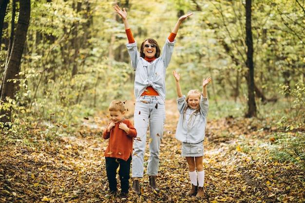 Mãe com seu filho e filha em um parque de outono