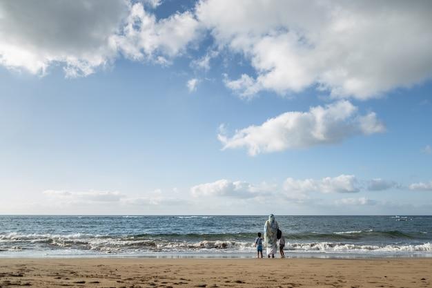 Mãe com seu filho e filha, olhando para o mar na praia de las canteras em gran canaria, ilhas canárias, espanha