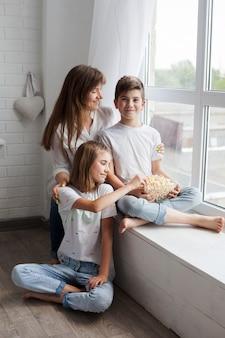 Mãe com seu filho e filha sentada perto da janela em casa
