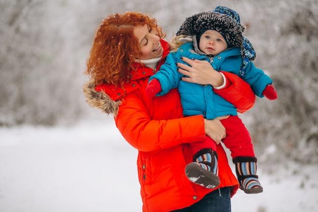 Mãe com seu filho pequeno juntos em um parque de inverno