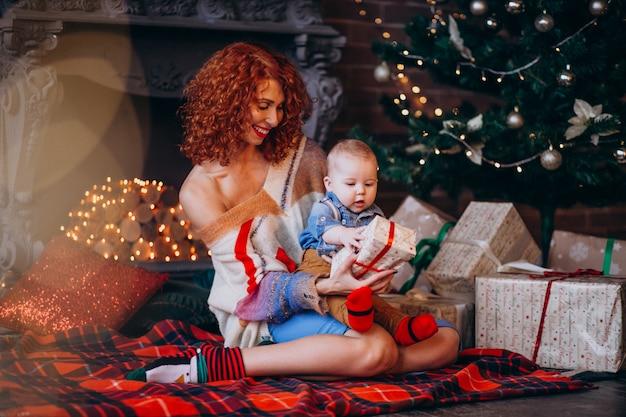 Mãe com seu filho pequeno pela árvore de natal com presentes