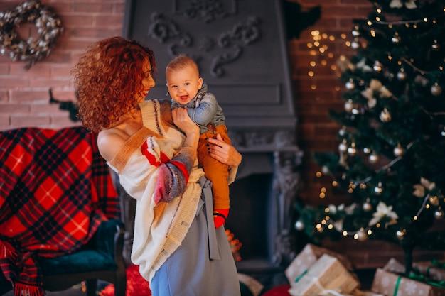 Mãe com seu filho pequeno pela árvore de natal