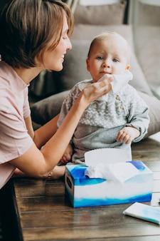 Mãe com seu filho pequeno usando guardanapos para corrimento nasal