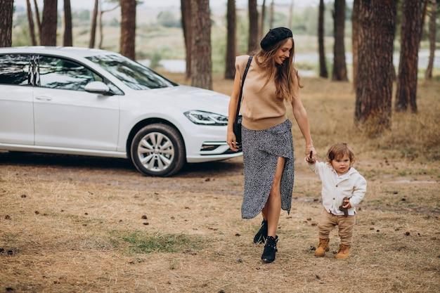 Mãe com seu filho perto do carro no parque