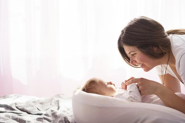Mãe com seu filho recém-nascido deitada na cama sob os raios de sol saindo pela janela