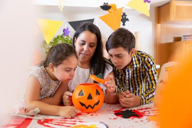 Mãe com seus dois filhos fazendo os preparativos em casa para a festa de halloween.