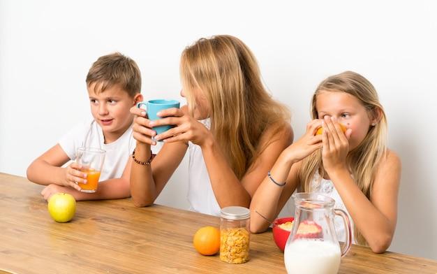Mãe com seus dois filhos tomando café da manhã