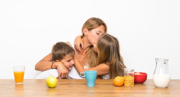 Mãe com seus dois filhos tomando café e abraçando