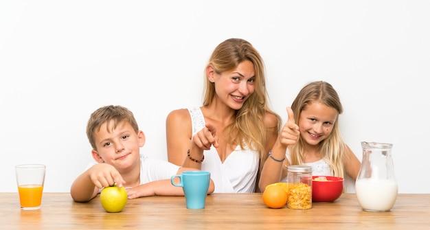 Mãe com seus dois filhos tomando café e apontando para a frente
