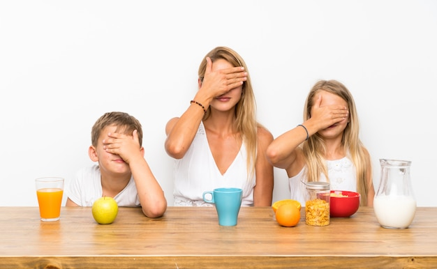 Mãe com seus dois filhos tomando café e cobrindo os olhos