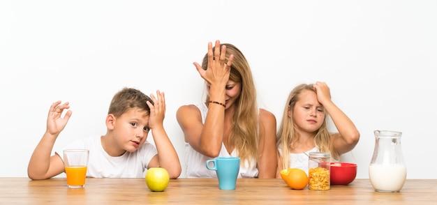 Mãe com seus dois filhos tomando café e tendo dúvidas