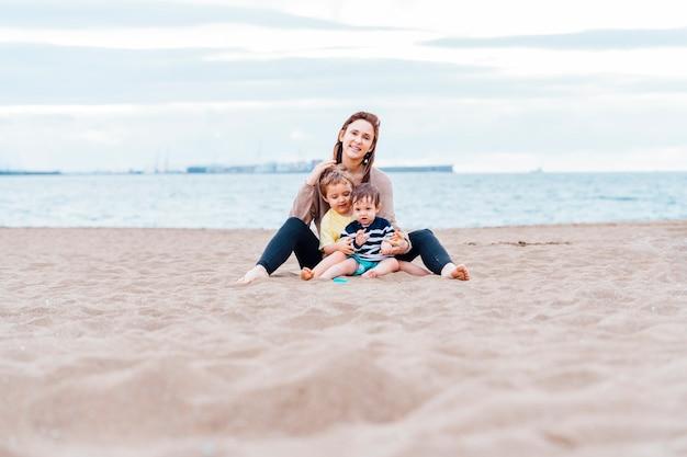 Mãe com seus filhos de um e três anos na praia em um dia nublado de verão. mãe solteira