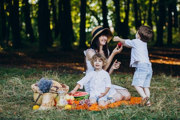 Mãe com seus filhos fazendo piquenique na floresta