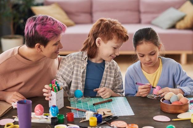 Mãe com seus filhos sentados à mesa e pintando ovos com giz de cera que estão preparando para a páscoa