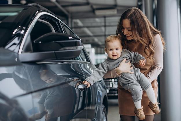 Mãe com sua filha bebê em um showroom de automóveis