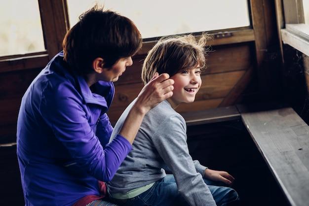 Mãe com sua filha de sete anos rindo em uma cabana na zona rural.