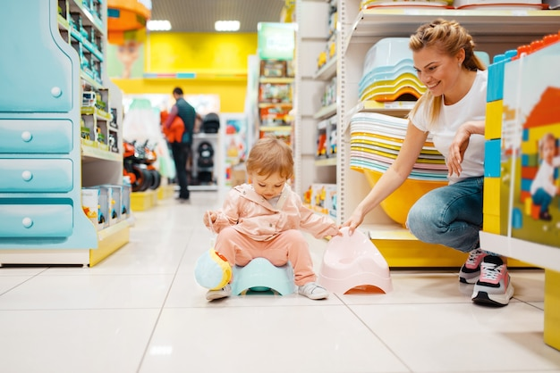 Mãe com sua filha escolhendo penico de bebê na loja de crianças.