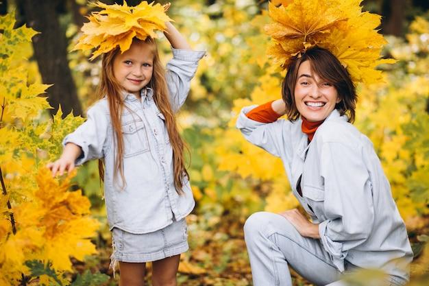 Mãe com sua filha na floresta cheia de folhas douradas