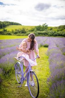 Mãe com sua filhinha em bicicleta roxa em fundo lavanda república tcheca