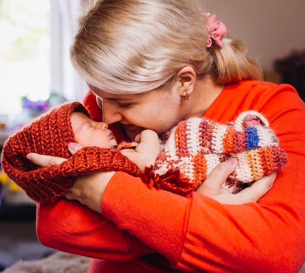 Mãe com suéter vermelho segura bebê recém nascido em seus braços