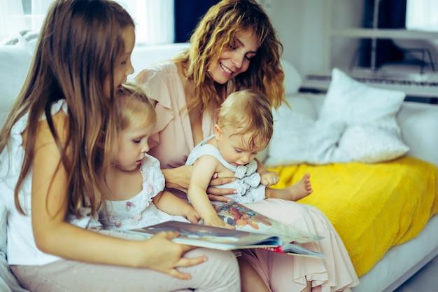 Mãe com três filhos, lendo um livro em uma atmosfera caseira