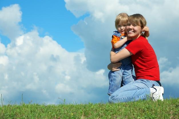Mãe com um abraço de sua filha na grama verde sob o céu azul