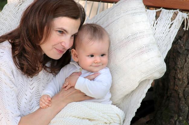 Mãe com um bebê andando em uma rede.