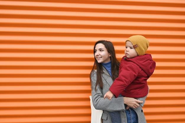Mãe com um bebê nos braços em roupas quentes em um fundo laranja