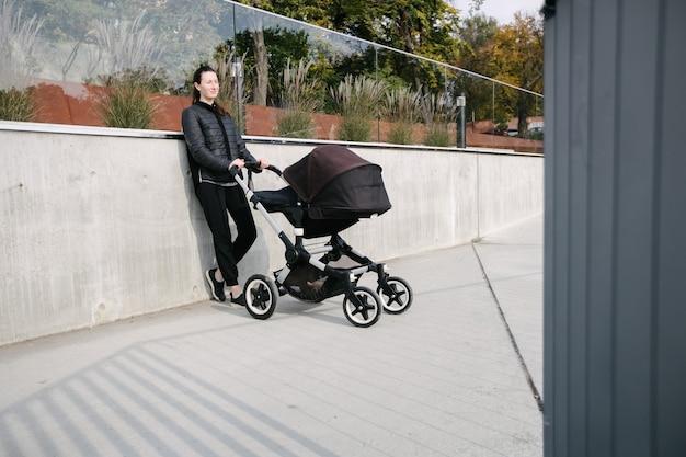 Mãe com um carrinho de bebê ou carrinho nas ruas da cidade moderna Foto Premium