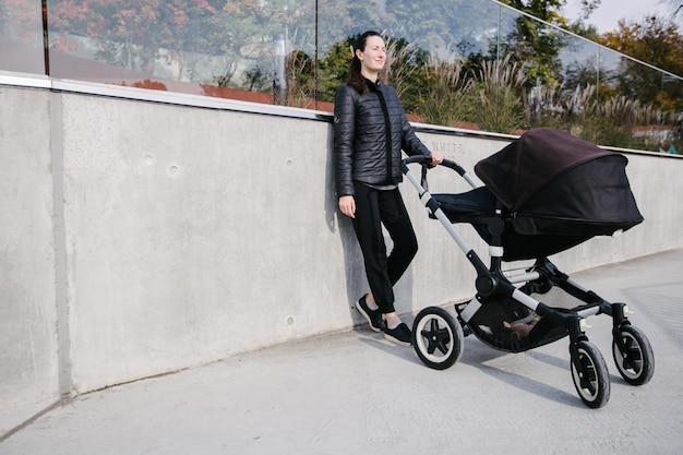 Mãe com um carrinho de bebê ou carrinho nas ruas da cidade moderna