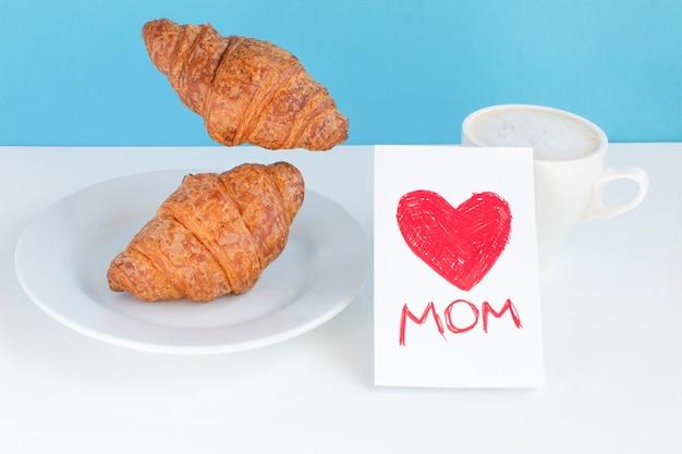 Mãe com um coração vermelho em um cartão, uma caneca branca e croissants em um prato e voando sobre fundo azul