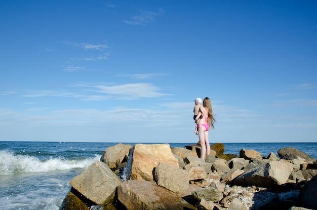 Mãe com um filho nas mãos na praia do mar estão entre as pedras