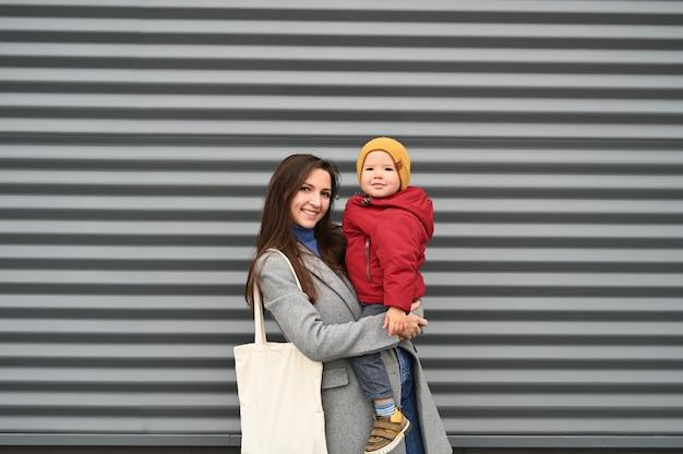 Mãe com um filho nos braços em roupas quentes em um fundo cinza