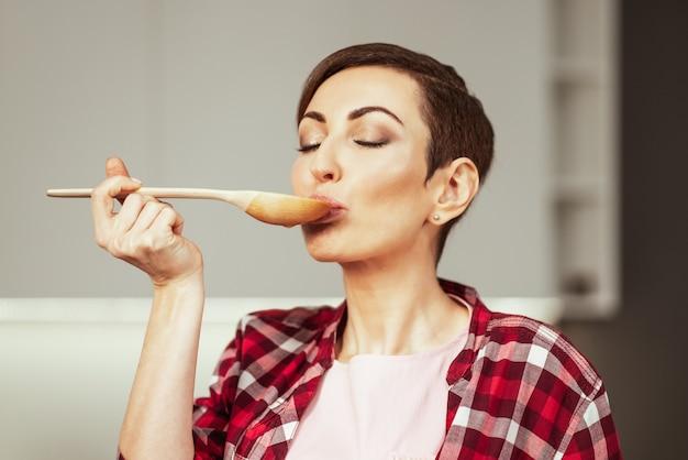 Mãe com um penteado curto testando uma comida enquanto cozinha um jantar para a família com os olhos fechados