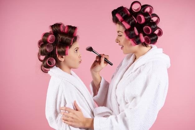 Mãe com um pincel nas mãos dela faz maquiagem para uma garotinha