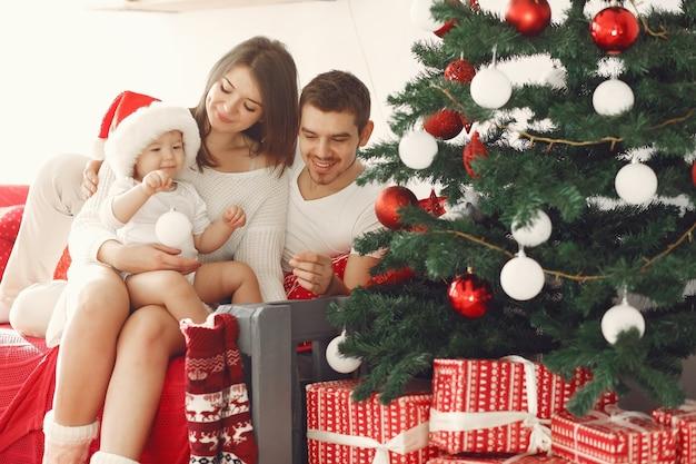 Mãe com um suéter branco. família com presentes de natal. criança com os pais em uma decoração de natal.