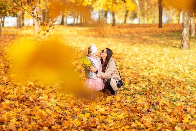 Mãe com uma filha bebê em roupas elegantes, com um beijo de câmera no fundo da folhagem de outono brilhante amarelo no parque. caminhada em família e sessão de fotos na natureza dourada do outono