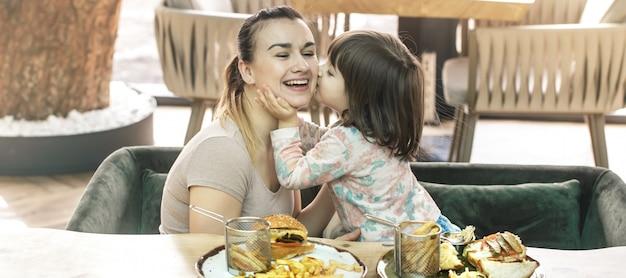 Mãe com uma filha bonitinha comendo fast-food em um café