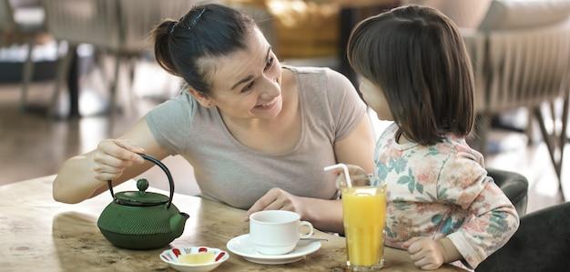 Mãe com uma filha pequena e fofa bebem chá e suco de laranja em um café, o conceito de valores familiares e família