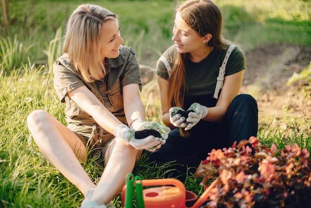 Mãe com uma filha trabalha em um jardim perto da casa