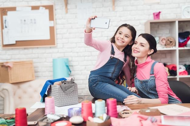 Mãe com uma garotinha fazer selfie em um smartphone.