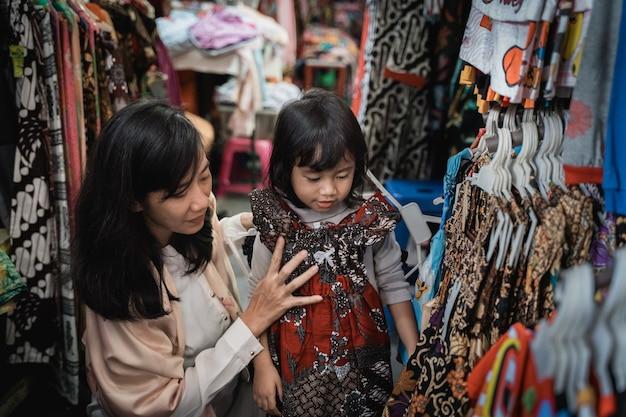 Mãe comprar e experimentar batik para sua filha