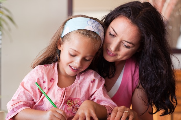 Mãe concentrada ajudando sua filha a fazer a lição de casa