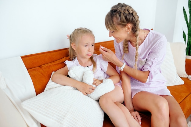 Mãe conforta menina sentada em um sofá em uma sala iluminada quando surgem problemas. menina segurando um ursinho de pelúcia branco
