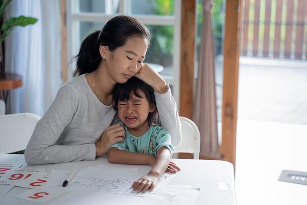 Mãe conforta sua filha chorando em casa