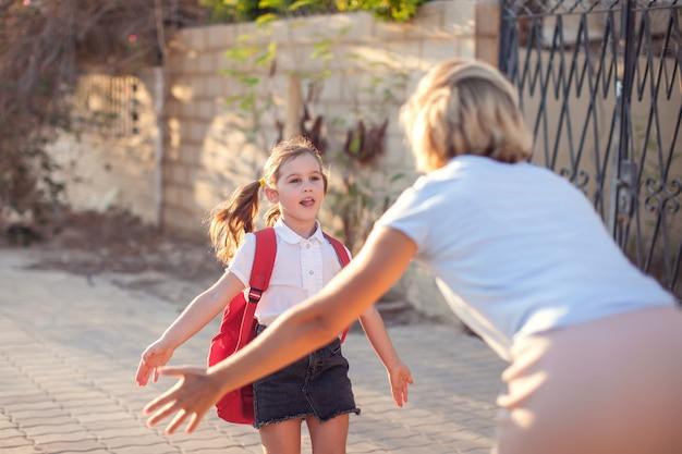 Mãe conhecendo aluno da escola. de volta à escola. relações entre pais e filhos.