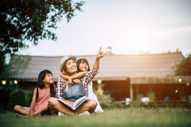 Mãe contando uma história para duas filhinha no jardim de casa