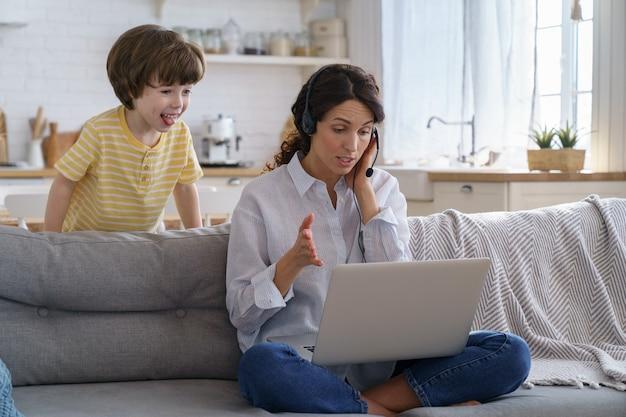 Mãe conversando em videochamada remota, trabalhando em um laptop de casa com uma criança, crianças fazendo barulho, mostrando a língua