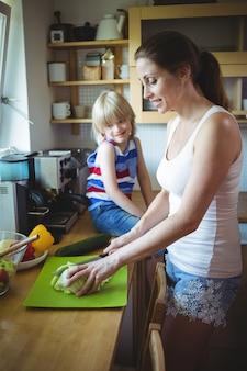 Mãe cortar legumes e filha olhando para ela